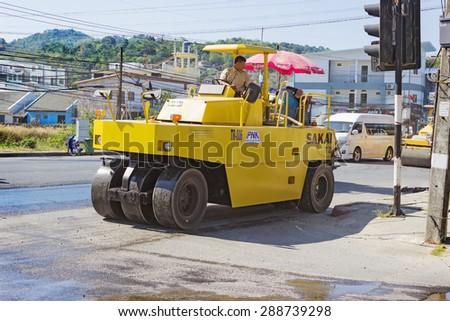 PHUKET, THAILAND - MAR 03, 2015: Workers operating asphalt paver machine and heavy machinery during repairs road - stock photo