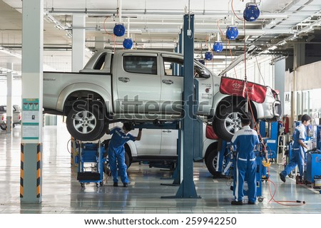 PHUKET, THAILAND - MARCH 10 : Car technician repairing car in workshop service station in Phuket on March 10, 2015. The official dealer of Toyota, who is the top market share for commercial car. - stock photo