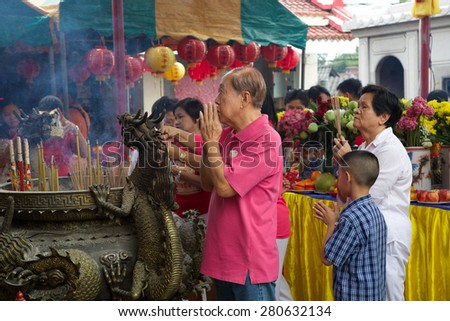 Phuket, Thailand - 6 March, 2015. Chinese New Year celebrations as a family light incense at a temple on the first day of the 3-day vacation. - stock photo