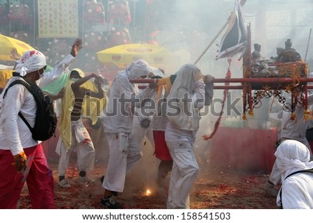 PHUKET, THAILAND - OCTOBER 12: A traditional scene of Thai devotees with fireworks in the street procession of the Phuket Vegetarian Festival in Phuket Town, Phuket, Thailand on 12th October, 2013.