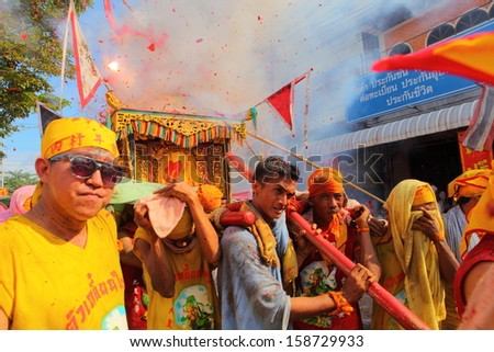 PHUKET, THAILAND - OCTOBER 12 : Unidentified devotees exploding firecrackers to respect god while participating in street procession of Phuket Vegetarian Festival on October 12, in Phuket, Thailand.