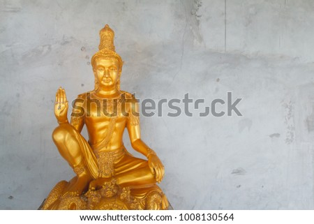 PHUKET, THAILAND - September 23, 2017 : Golden buddha statue. The statue on the background of a cracked gray wall.