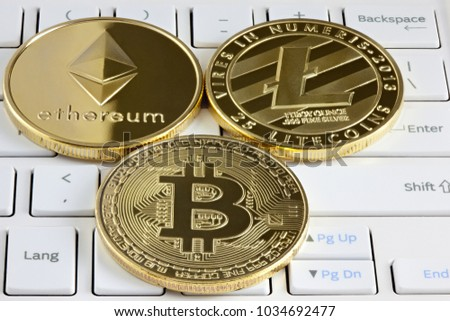 Physical golden bitcoin, ethereum and litecoin coin lying on computer keyboard.