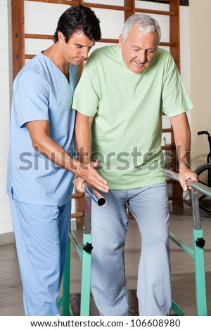Physical therapist assisting senior man to walk with the support of bars at hospital gym - stock photo