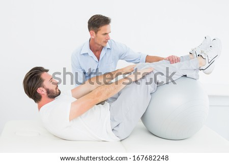 Physical therapist assisting young man do sit ups in the gym at hospital - stock photo