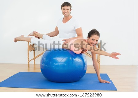 Physical therapist assisting young woman with yoga ball in the gym at hospital