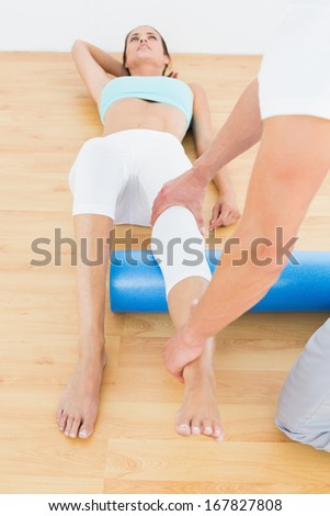 Physical therapist examining a young woman's leg at the hospital gym - stock photo