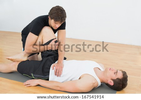 Physical therapist examining young mans leg at the hospital gym