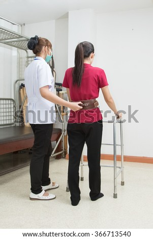 Physical therapist helping patient to walk using walker in hospital,  physical rehabilitation therapy - stock photo