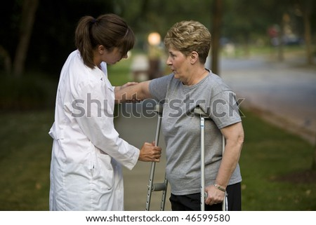 Physical therapist helps a patient with crutches