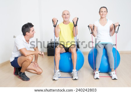 Physical therapist showing skipping rope exercise to a couple of seniors
