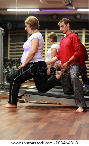 Physical therapist stretching ,pregnant woman's leg in gym - stock photo