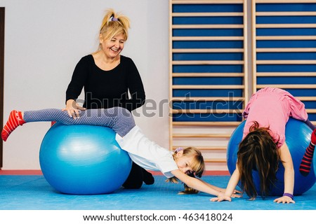 Physical therapist working with little girls in school gymnasium, exercising with fitness ball