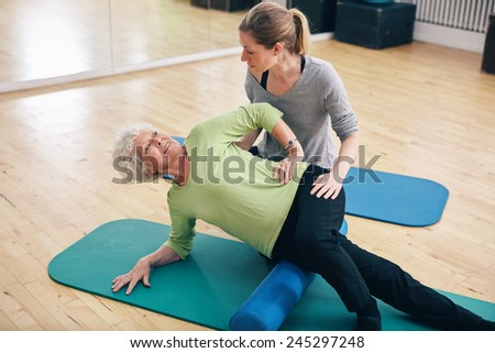 Physical therapists assisting senior woman to perform myofascial release technique with a foam roller to inhibit overactive muscles at gym. - stock photo