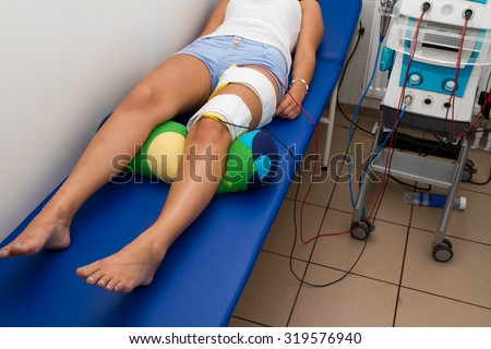 Physical therapy , woman with eletrical stimulator for increase muscle strength and release pain - stock photo