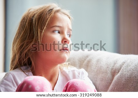 Physically Abused Child At Home Sitting On Sofa - stock photo