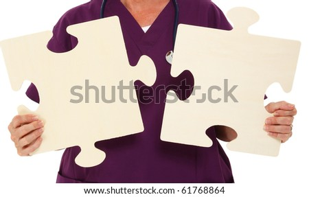 Physician Holding Puzzle Pieces Over White Background - stock photo