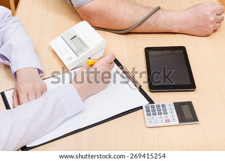physician measures blood pressure of patient during appointment - stock photo