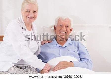 Physician with her elderly patient recovering in bed  - stock photo