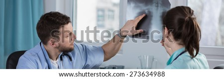 Physicians looking at x-ray photo of lungs - stock photo