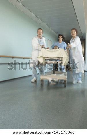 Physicians rushing patient on gurney down hospital corridor - stock photo