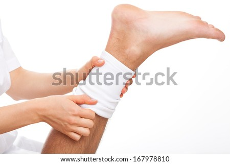 Physioterpist putting an elastic band on injured leg of patient - stock photo