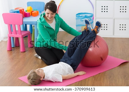 Physiotherapist and boy lying on foam mattress, exercising on gym ball
