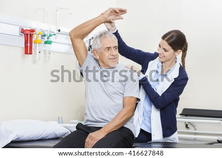 Physiotherapist Assisting Senior Man To Exercise