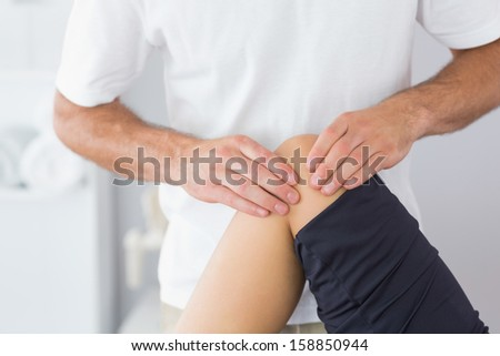 Physiotherapist checking knee of a patient in bright office