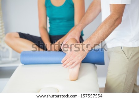 Physiotherapist checking patients leg in bright office