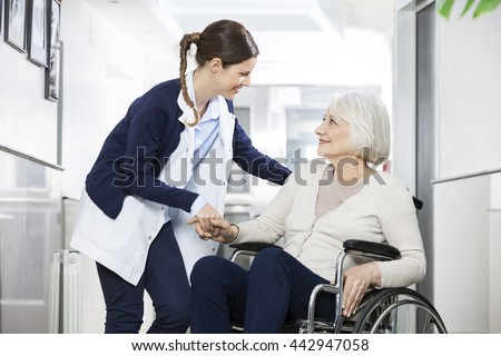 Physiotherapist Consoling Senior Woman Sitting In Wheelchair - stock photo