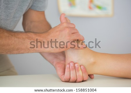 Physiotherapist controlling patients foot in bright office - stock photo