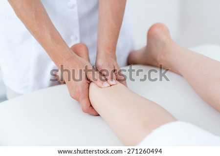 Physiotherapist doing leg massage in medical office
