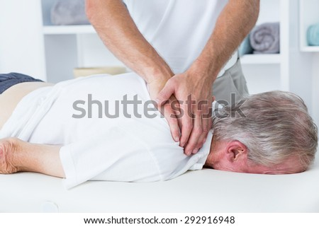 Physiotherapist doing shoulder massage to his patient in medical office - stock photo