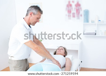 Physiotherapist doing stomach massage to his patient in medical office