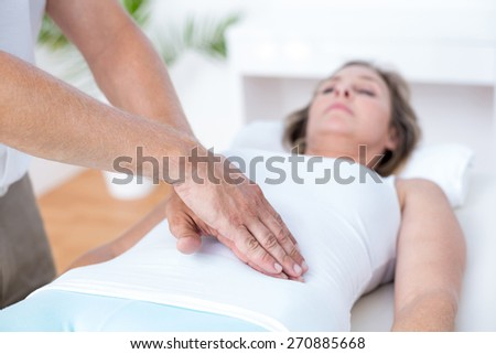 Physiotherapist examining his patients stomach in medical office - stock photo