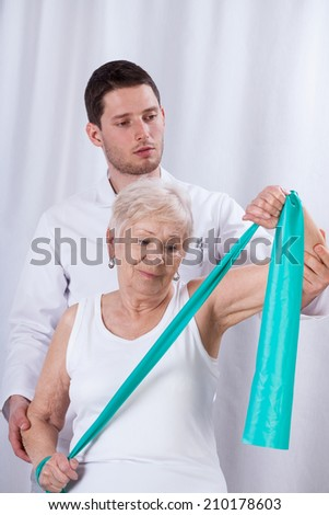 Physiotherapist exercising with elderly patient with elastic band