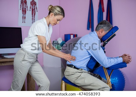 Physiotherapist giving back massage to a patient in the clinic
