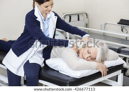 Physiotherapist Giving Massage To Senior Woman In Rehab Center