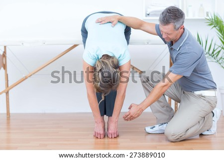 Physiotherapist helping his patient stretching in medical office - stock photo