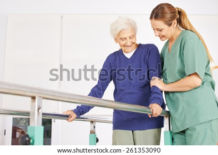Physiotherapist helping old senior woman on treadmill with handles - stock photo
