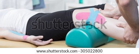 Physiotherapist is conducting leg rehabilitation on his patient - stock photo