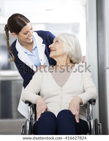 Physiotherapist Looking At Senior Patient Sitting In Wheelchair - stock photo