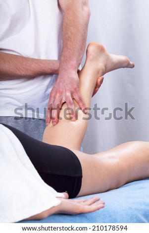 Physiotherapist making the massage of tense calf - stock photo