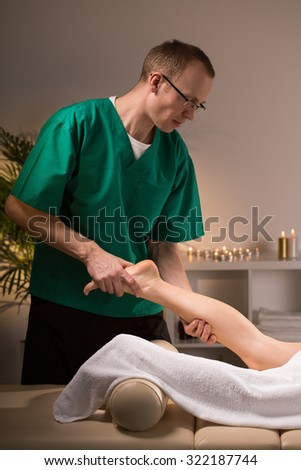 Physiotherapist massaging female leg in spa room