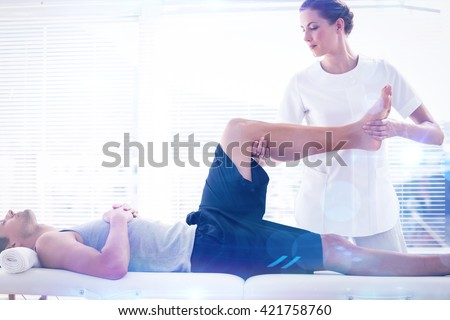 Physiotherapist massaging leg of man against lens flare