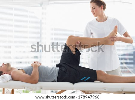 Physiotherapist massaging leg of young man at spa - stock photo