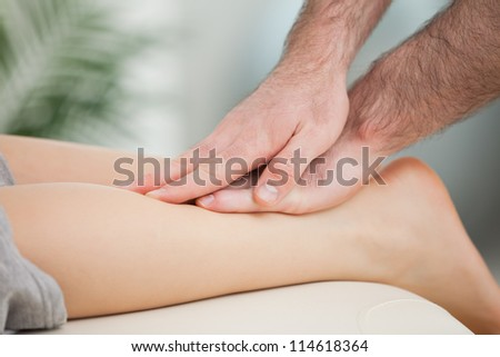 Physiotherapist massaging the calf of a woman in a room - stock photo
