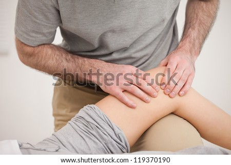 Physiotherapist massaging the knee of a woman in a room - stock photo