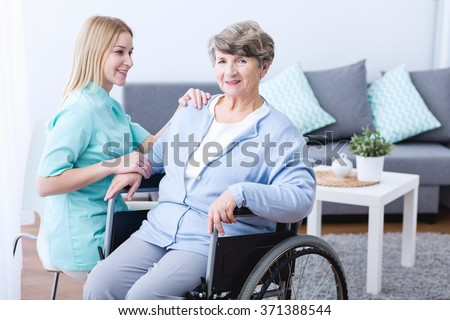 Physiotherapist rehabilitating senior woman sitting in a wheelchair - stock photo